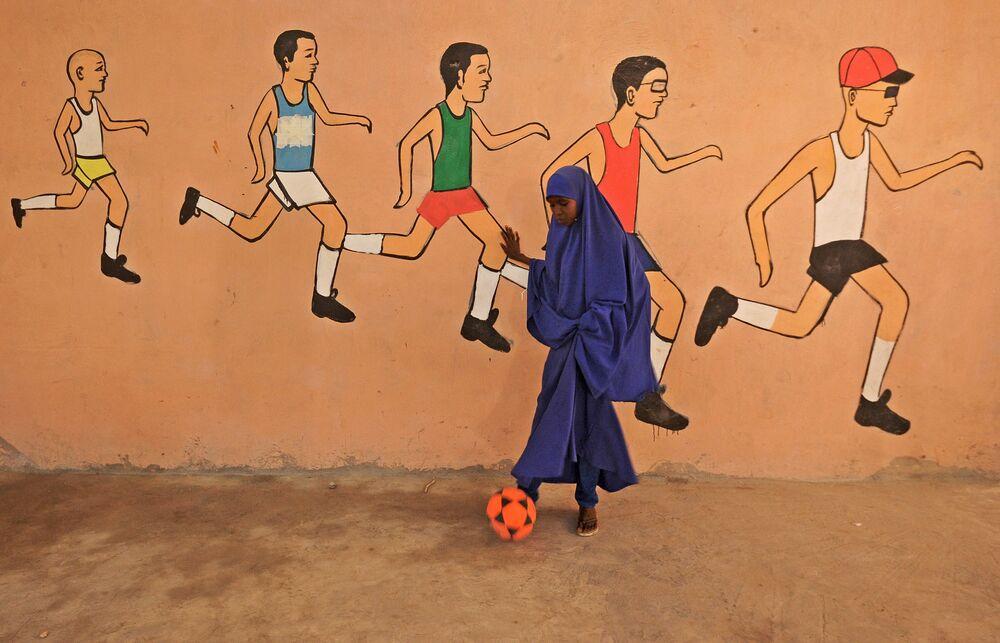 Menina com bola em escola de Mogadíscio, Somália