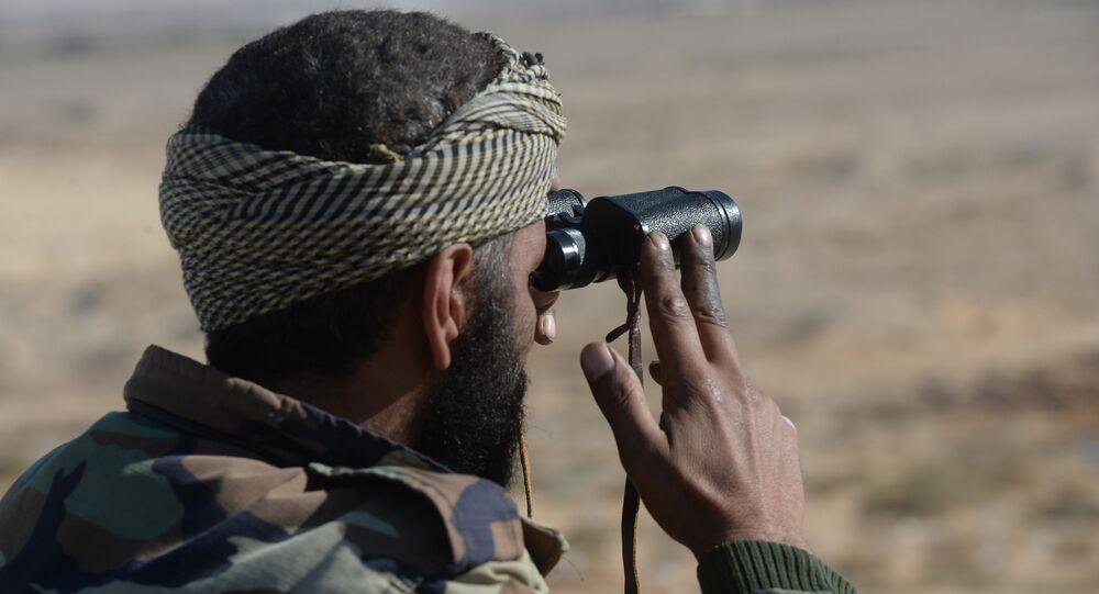 Um soldado do Exército Sírio está vigilando as posições dos militantes, a 20 km de Palmira, na Síria