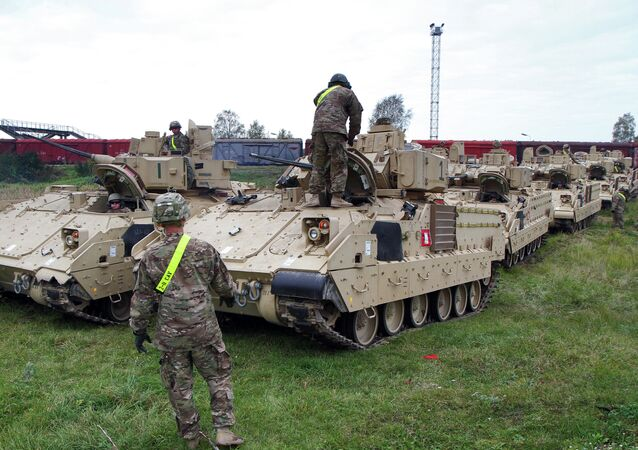 Members of the US Army 1st Brigade, 1st Cavalry Division, unload Bradley Fighting Vehicles at the railway station near the Rukla military base in Lithuania, on October 4, 2014