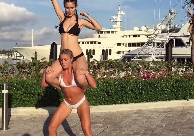 Swedish fitness model Katarina Konow SQUATTING her swimsuit model sister on her back