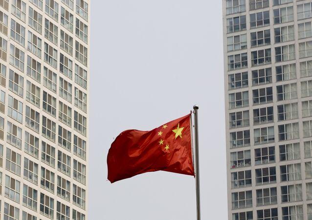 Uma bandeira nacional chinesa vibra no vento entre um complexo residential de grande altura e do escritório em Pequim,  China (foto de arquivo)
