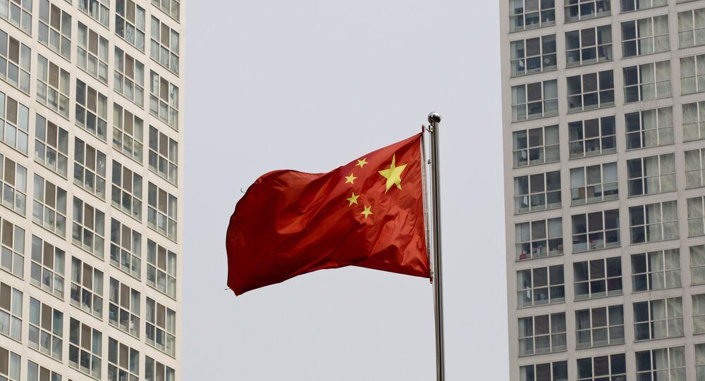 Uma bandeira nacional chinesa vibra no vento entre um complexo residential de grande altura e do escritório em Pequim,  China (arquivo)