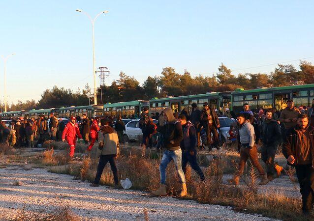 Os evacuados do leste de Aleppo desembarcam dos ônibus após sua chegada à cidade de al-Rashideen, que é mantida pelos insurgentes, na Síria, em 15 de dezembro de 2016.