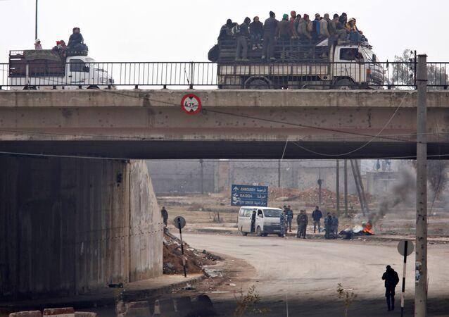 Comboio com civis retirados do leste de Aleppo passando pela ponte de al-Ramousah nesta sexta-feira, 16 de dezembro de 2016