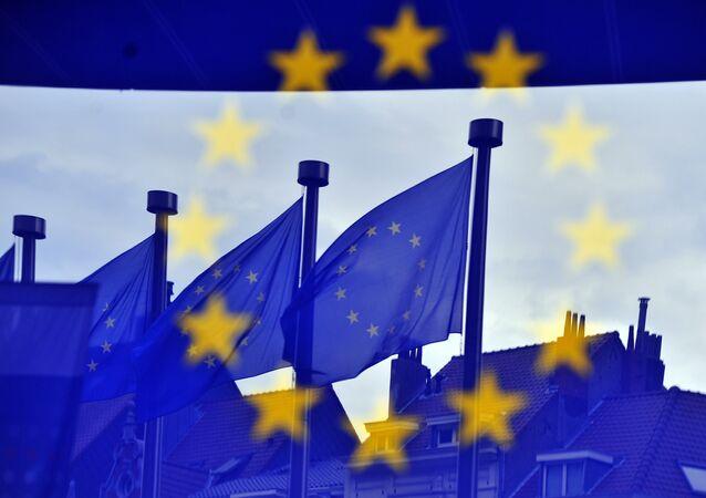 Bandeiras da União Europeia refletidas na entrada do Edifício Berlaymont, sede da Comissão Europeia, em Bruxelas