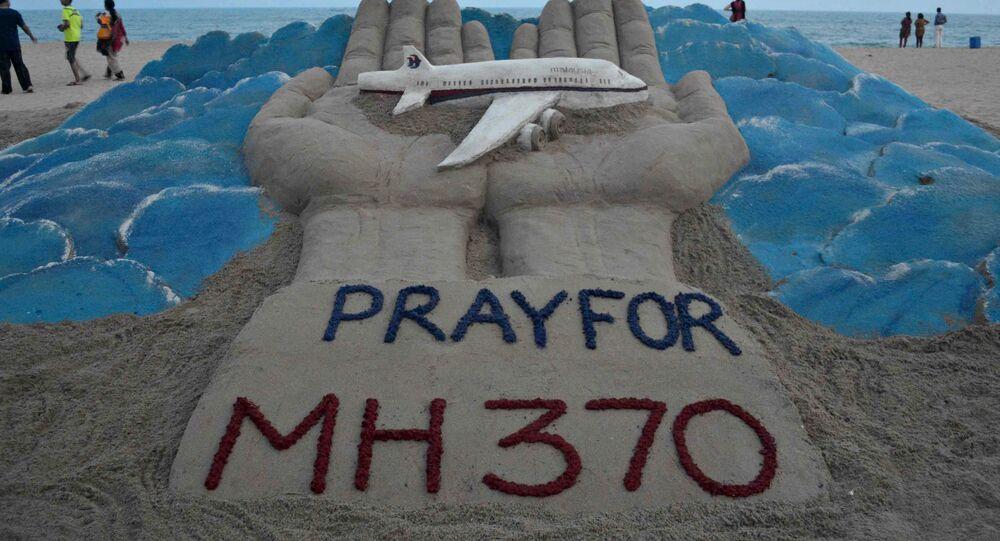 Banhistas passam por escultura de areia com mensagem de orações pelo voo perdido da Malaysian Airlines MH370