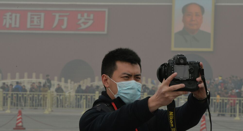 A Chinese tourists takes a photo while wearing a face mask in Tiananmen Square as heavy air pollution continues to shroud Beijing on February 26, 2014