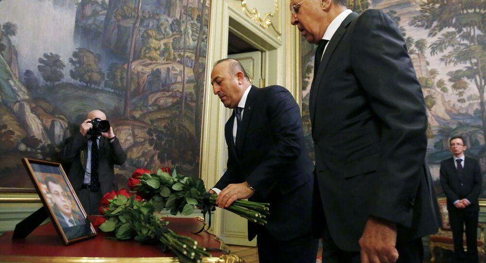 Ministro das Relações Exteriores da Rússia, Sergei Lavrov, e seu colega turco, Mevlut Cavusoglu, depositam flores em frente à foto do embaixador da Rússia na Turquia, assassinado em Ancara