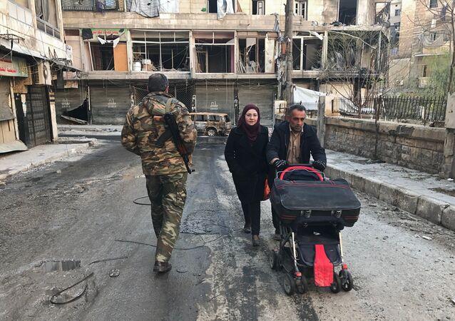 Civis caminham por rua de Aleppo após a libertação da cidade pelo Exército Sírio
