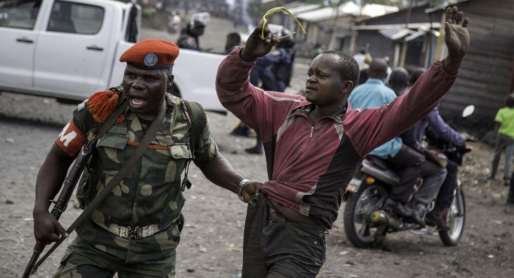 Policial militar segura detido que participou de manifestação, RD do Congo