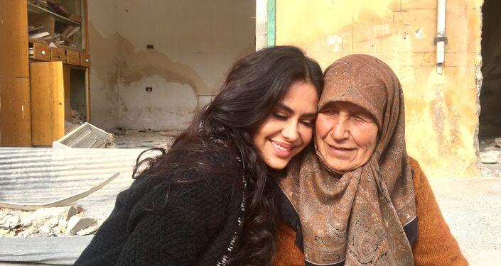 Cineasta boliviana Carla Ortiz junto a uma idosa na Síria