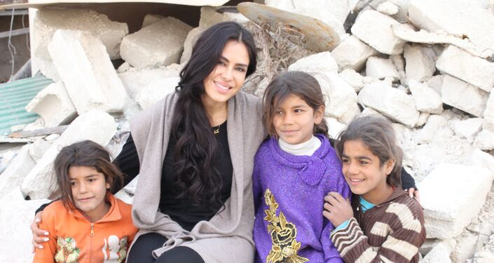 Carla Ortiz numa foto conjunta com crianças sírias