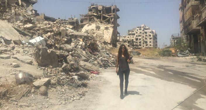 Carla Ortiz caminha entre prédios destruídos da cidade
