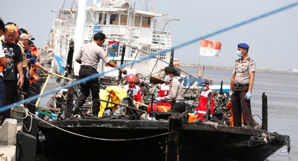 Polícia e Cruz Vermelha resgatam as pessoas depois do incêndio em um barco na Indonésia. Janeiro,1. 2017