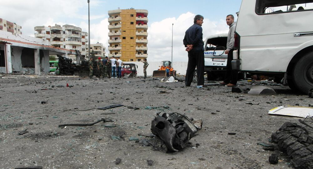 Syrians gather at the scene of multiple bombings in the the city of Tartus northwest of Damascus. File photo
