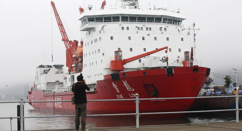 Homem tira fotografia do quebra-gelo chinês Xuelong (Dragão de Neve)