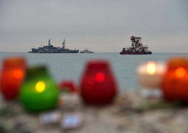 Velas em homenagem às vítimas da queda do avião russo. Ao fundo, navios da Marinha russa realizam busca dos escombros do Tu-154 no mar Negro, Rússia, 27 de dezembro de 2016