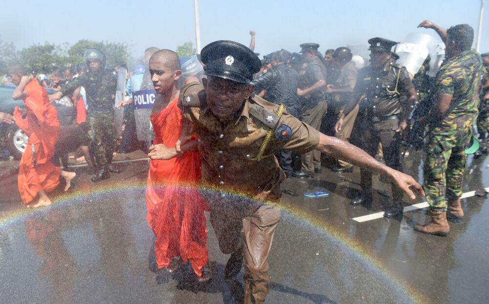 Policial leva um monge durante protesto ocorrido em Sri-Lanka