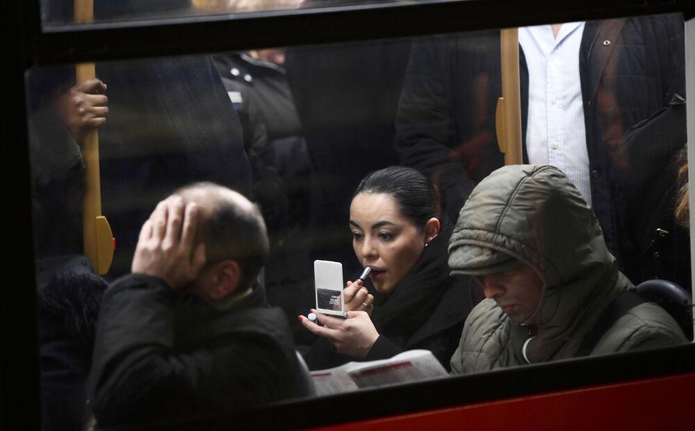 Uma mulher faz maquiagem em ônibus lotado em Londres