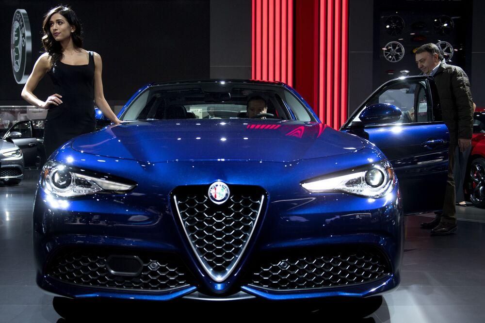 Modelo perto de um carro Alfa Romeo Giulia na exposição de automóveis realizada em Detroit