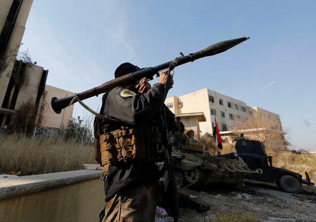 Um membro das Forças de Operações Especiais do Iraque (ISOF) carrega um lançador de foguetes na Universidade de Mossul durante uma batalha contra militantes do Daesh (Estado Islâmico). Mossul, Iraque, 14 de janeiro de 2017