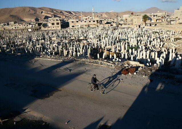 Civil anda de bicicleta ao lado de cemitério em Douma, ocupada por rebeldes, nos arredores de Damasco, Síria, 3 de janeiro de 2017