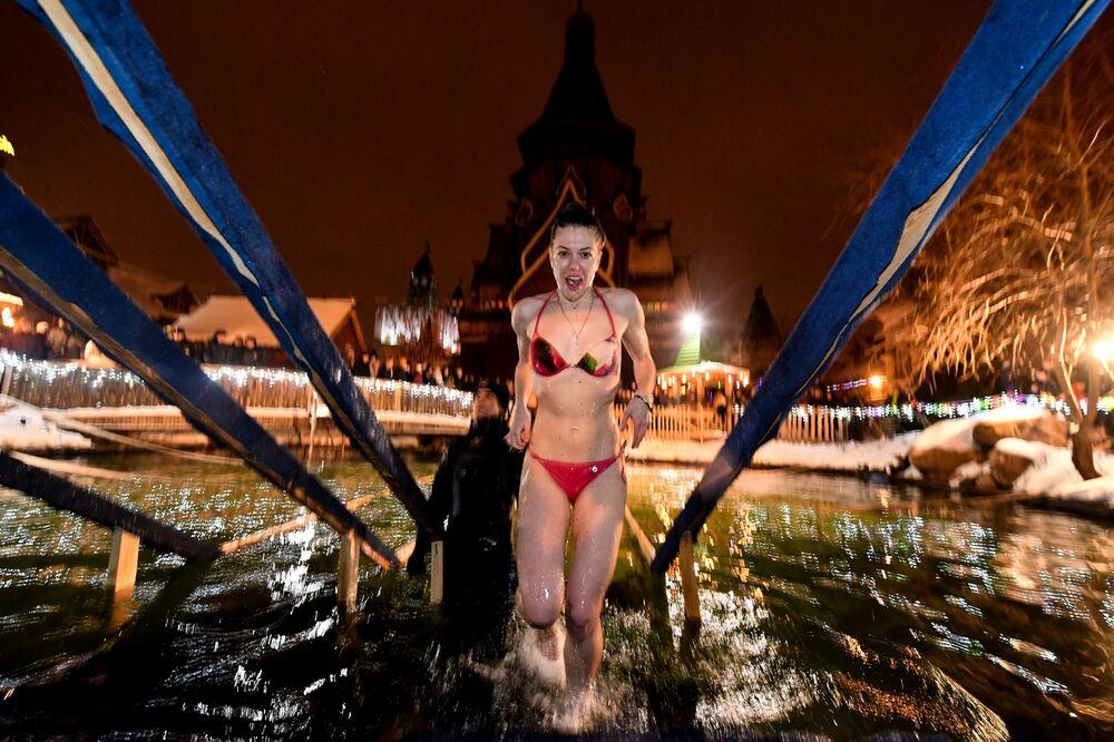 Menina toma banho em água gelada de acordo com costume da Igreja Ortodoxa