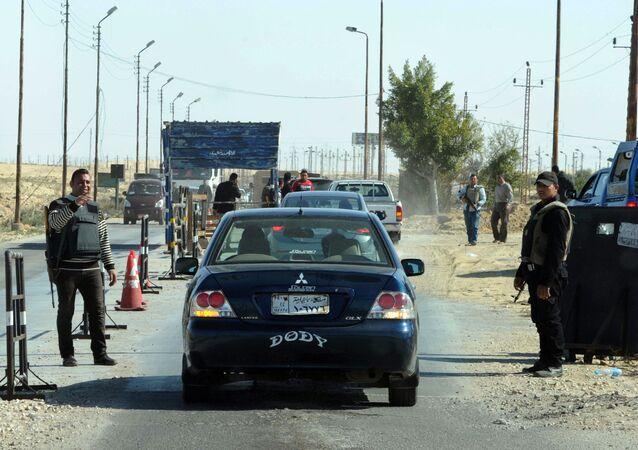Polícia egípcia inspecionando carros em posto de controle no Sinai do Norte.