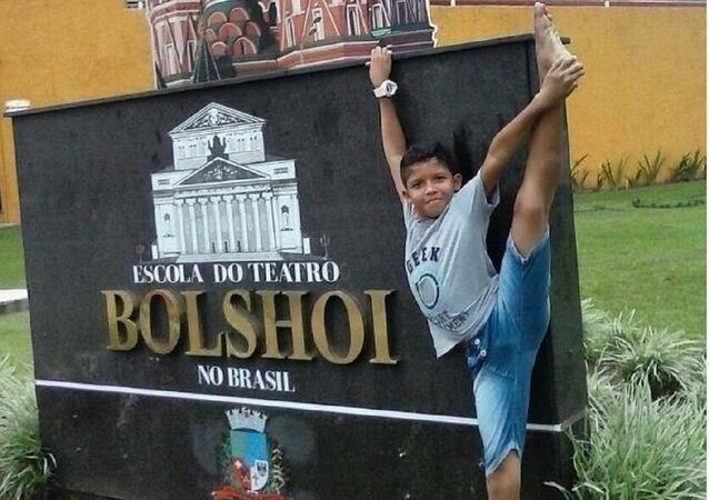 O menino Adrian Barreto junto à placa da Escola Bolshoi Brasil