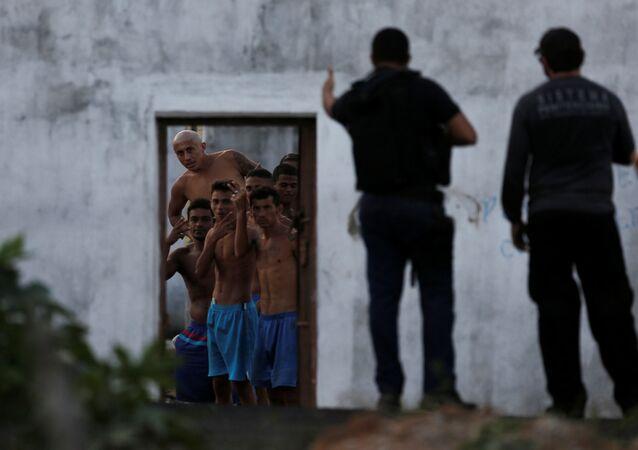 Prisioneiros gesticulam à polícia que lhes trouxe a comida na prisão brasileira de Alcaçuz, durante os motins.