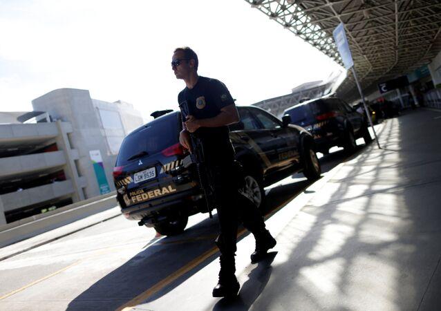 Agente da Polícia Federal espera no aeroporto do Galeão, no Rio de Janeiro