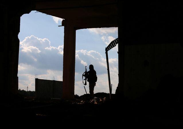 Lutador do Exército Sírio Livre carrega sua arma enquanto está de pé em um prédio danificado, no leste da cidade rebelde de Dael, em Deraa Governorate, Síria, 3 de janeiro de 2017