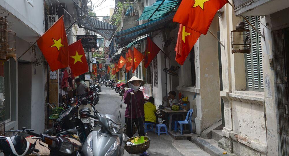 Moça comerciante na Rua de Hanoi condecorada em homenagem ao Dia da Nação, festejado no dia 2 de setembro.