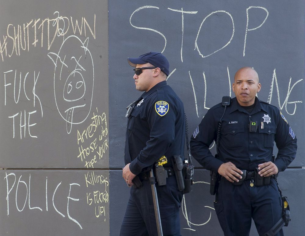 Oficiais de polícia perto de grafittis contra eles, em Oakland