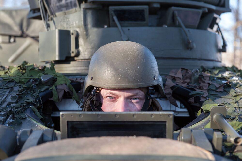 Militar num veículo ligeiro de reconhecimento FV107 SCIMITAR (Grã-Bretanha) durante a demonstração de material militar e armamento da OTAN na Letônia