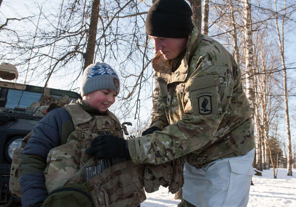 Menino prova colete à prova de balas durante a demonstração de material militar e armamento da OTAN na Letônia