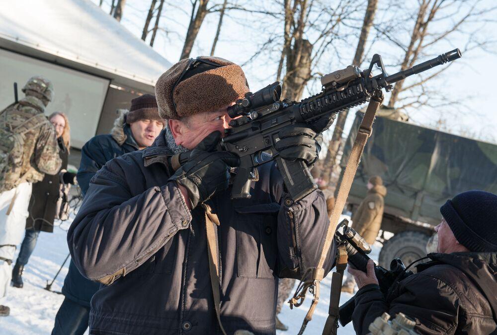 Residente local com fuzil M-16 durante a demonstração de material militar e armamento da OTAN na Letônia