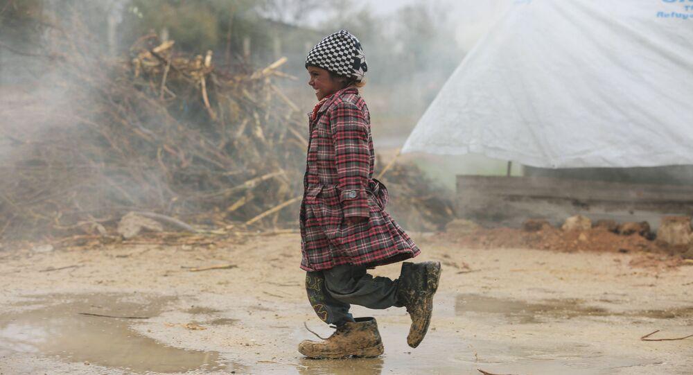Menina síria deslocada passeia pelo campo de refugiados na região da planície de Damasco.