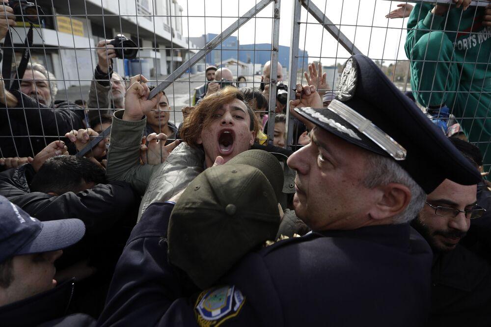 Polícia enfrenta imigrantes afegãos em Atenas após estes terem bloqueado a entrada do campo de refugiados Hellenikon devido à visita do ministro de Migração Yannis Mouzalas.