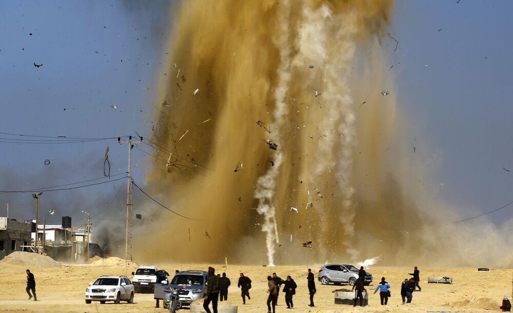 Palestinos correm para um refúgio em meio da fumaça após um ataque aéreo israelense contra um centro da organização palestina Hamas.