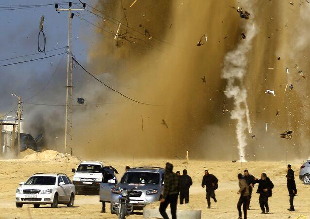 Palestinos correm para um refúgio em meio da fumaça após um ataque aéreo israelense contra um centro da organização palestina Hamas