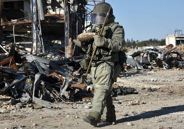 Sapador do Centro Internacional Anti-Minas das Forças Armadas russas desativa minas em Aleppo.