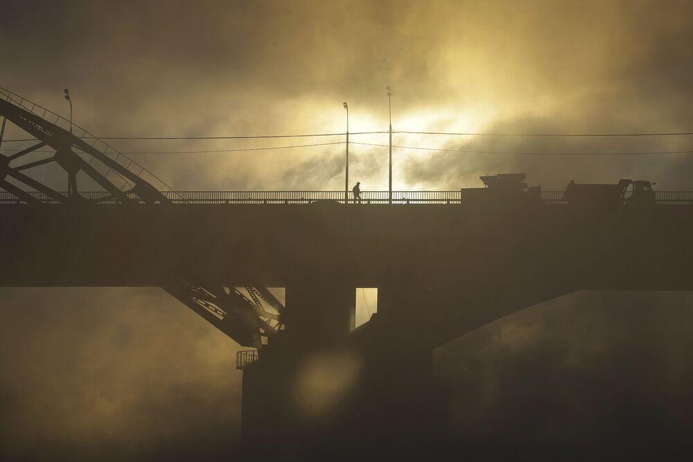 Pedestre atravessa uma ponte sobre o rio Moscou em uma manhã gelada.
