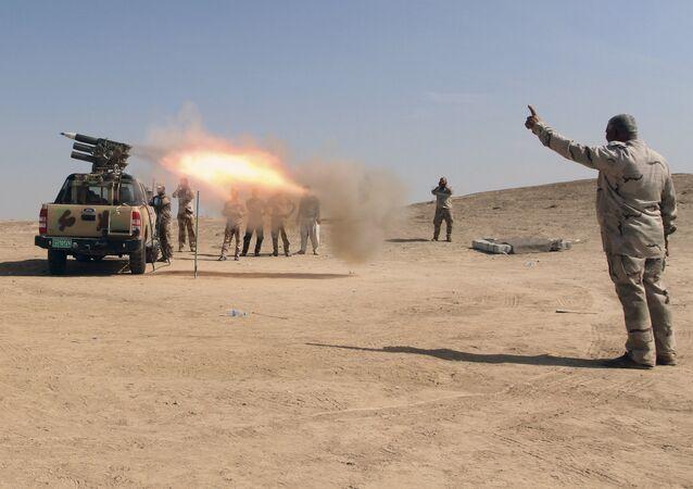 Forças de segurança iraquianas e Forças de Mobilização Popular suas aliadas disparam foguetes contra posições do Daesh em um campo petrolífero fora de Beiji, a cerca de 250 quilômetros ao norte de Bagdá, no Iraque, no sábado, 24 de outubro de 2015