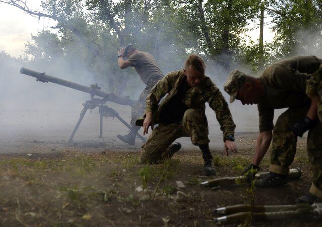 Soldados ucranianos gritam de um lançador de granadas antitanque SPG-9 durante o combate com os separatistas pró-russos perto de Avdeevka, região de Donetsk, em 18 de junho de 2015