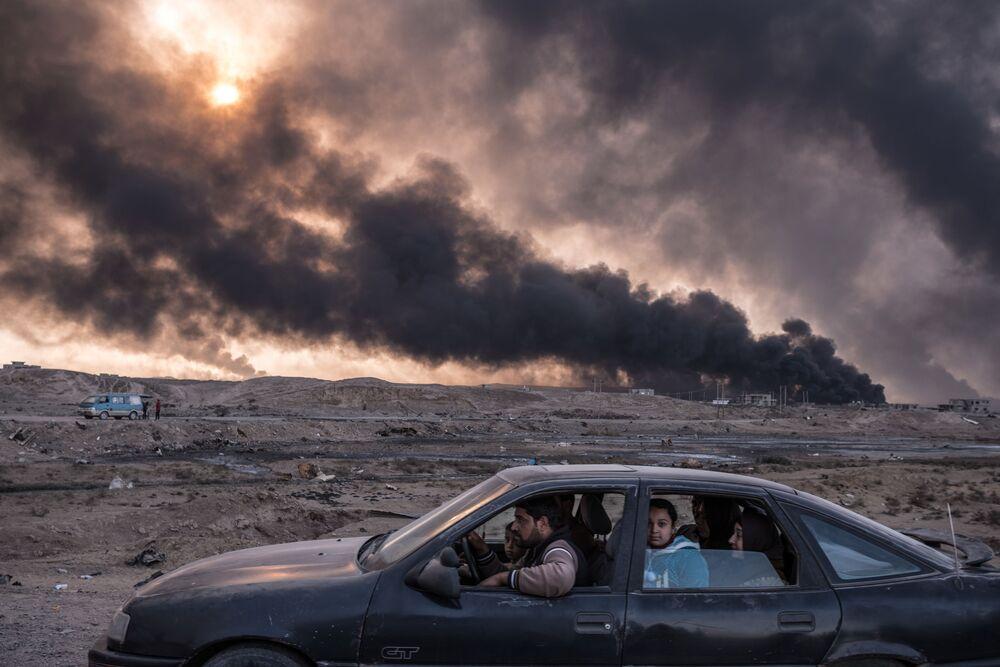 Foto da série Batalha Iraquiana para Recuperar suas Cidades de Sergei Ponomarev retrata uma família escapando às hostilidades em Mossul, segunda maior cidade do Iraque e um dos baluartes do Daesh