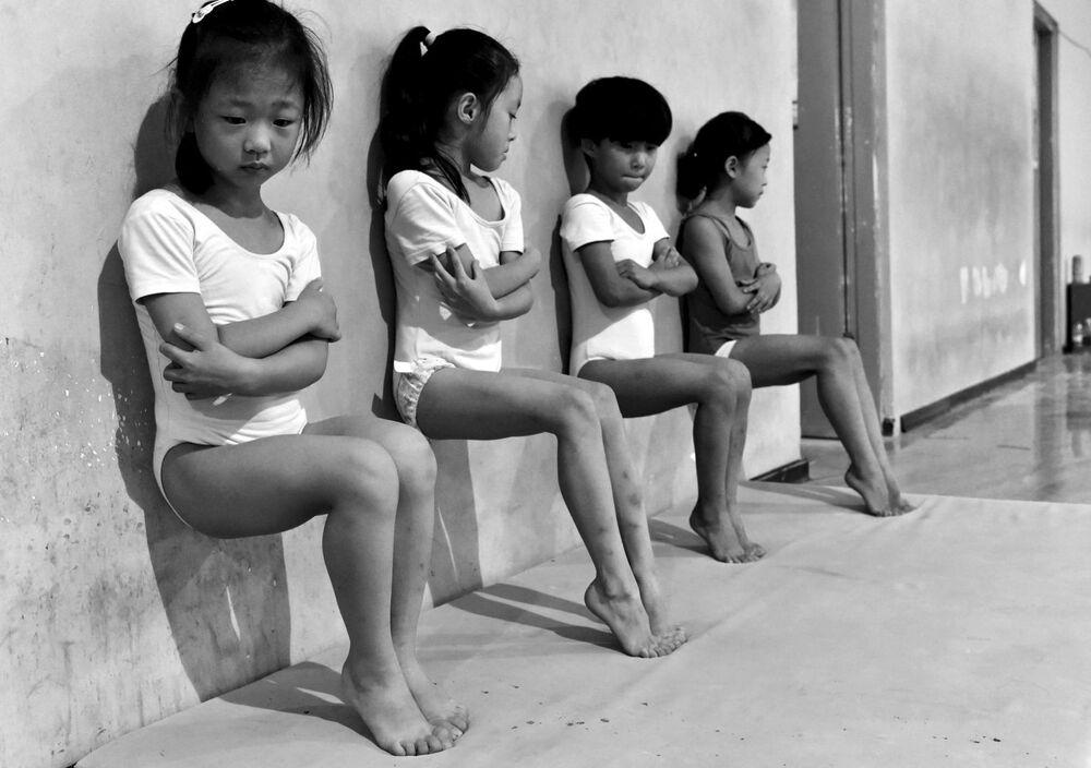 Imagem Suor Cria Campeões, do fotógrafo Tiejun Wang, apresenta quatro estudantes de uma escola de ginástica em Xuzhou, na China, fazendo treinamento de dedos por meia-hora cada di