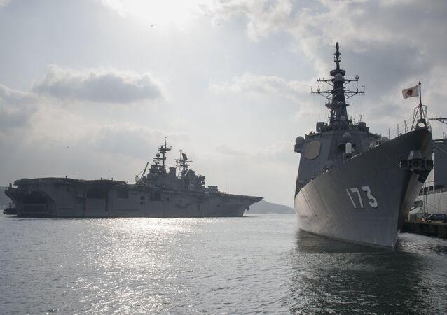O USS Bonhomme Richard acaba de zarpar, passando junto ao navio ancorado JS Kongo, em 30 de janeiro de 2017