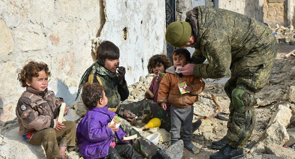 Engenheiros militares do centro internacional de desminagem do Exército russo continuam a operação no leste de Aleppo, na Síria. Foto mostra um soldado russo junto a crianças sírias