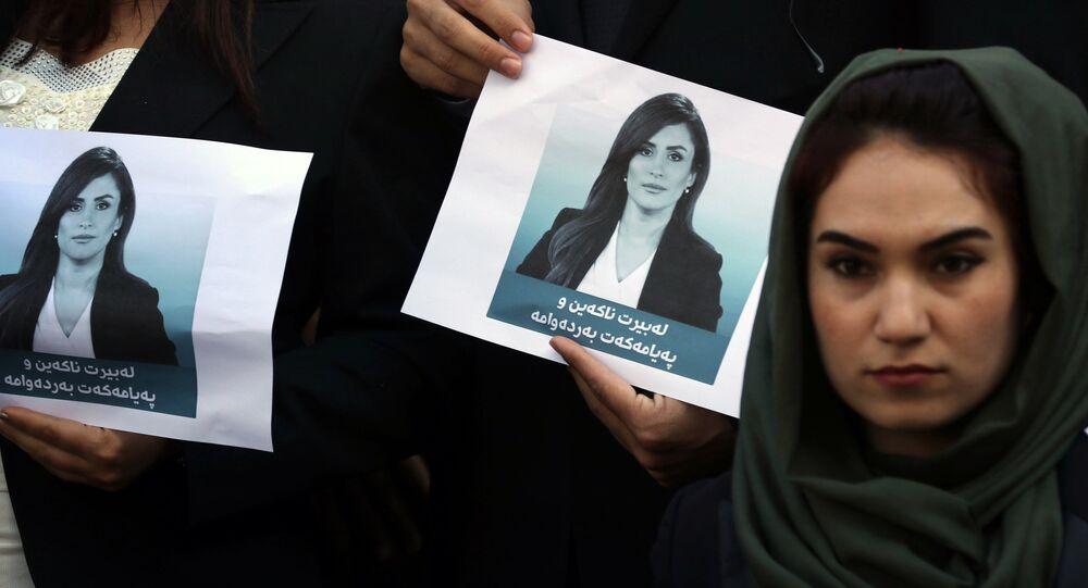Estudantes da Escola de Jornalismo de Arbil seguram retratos de Shifa Gardi em homenagem à jornalista morta em uma explosão no Iraque